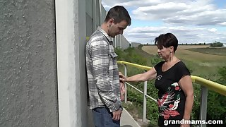 Mature woman over 60 gives a blowjob to hot young guy outdoor